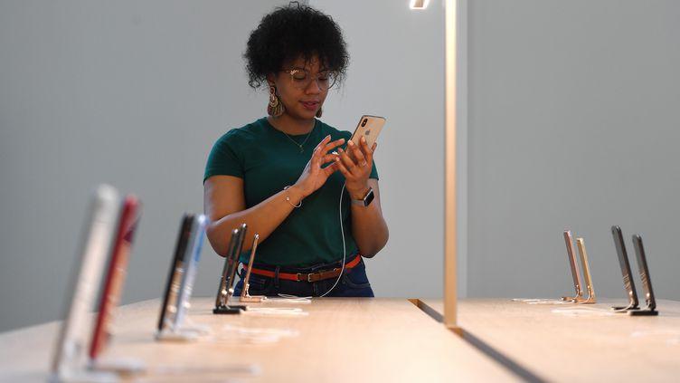 Une employée d'Apple utilise un iPhone lors de l'ouverture d'un magasin à Washington (Etats-Unis), le 9 mai 2019. (CLODAGH KILCOYNE / REUTERS)