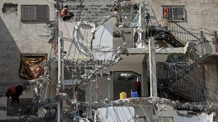 Des ouvriers palestiniens retirent des débris de la tour Al-Daour, qui menace de s'effondrer, le 10 août 2021, après avoir été bombardé par les forces israéliennes en mai. (MOHAMMED ABED / AFP)