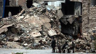 Des soldats devant un immeuble bombardé à Alep-Est, le 16 décembre 2016. (MAXPPP)