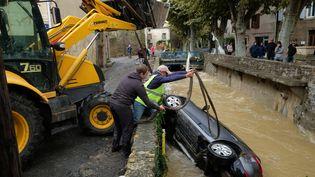 Une voiture est retirée d'un cours d'eau, le 15 octobre 2018, à Villegailhenc (Aude), après des inondations dévastatrices. (ERIC CABANIS / AFP)