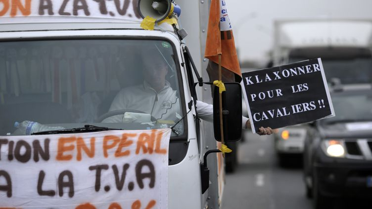 Un homme manifeste au volant de son camion contre la hausse de la TVA sur les centres équestres, le 2 décembre 2013, à Paris. (KENZO TRIBOUILLARD / AFP)