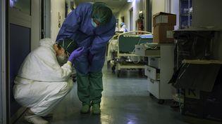 Le personnel soignant est harassé par la tâche immense. Une infirmière en réconforte une autre dans les couloirs de l'hôpital de Crémone (Italie), le 13 mars 2020. (PAOLO MIRANDA / AFP)
