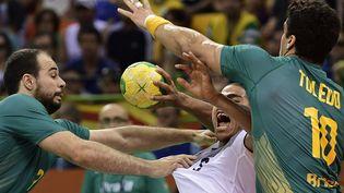 Le handballeur français Daniel Narcisse mis à mal par deux Brésiliens en quart de final des JO de Rio, le 17 août 2016 à Rio de Janeiro (Brésil). (JAVIER SORIANO / AFP)