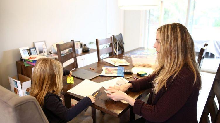 Une mère américaines'occupe de sa fille, dont l'école est fermée en raison de l'épidémie de Covid-19, en Californie, le 18 mars 2020. (EZRA SHAW / GETTY IMAGES NORTH AMERICA / AFP)