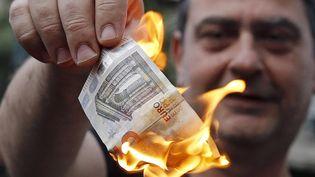 Un manifestant anti-austérité brûle un billet de 5 euros, le 28 juin 2015, à Athènes (Grèce). ( ALKIS KONSTANTINIDIS / REUTERS)