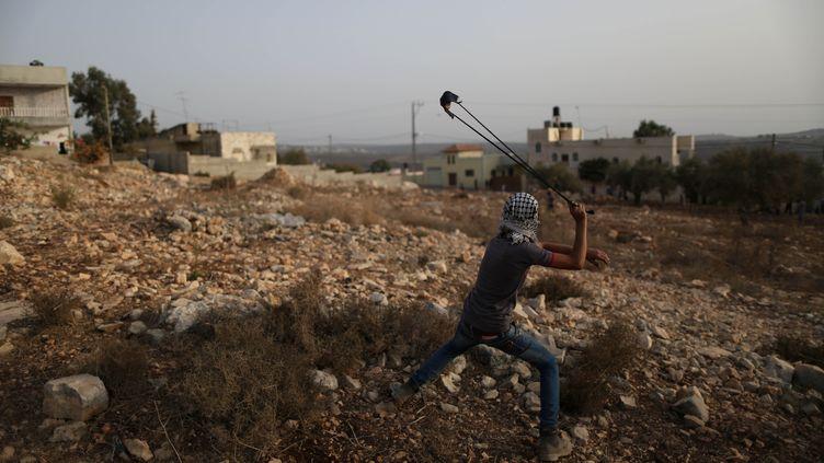 Un jeune Palestinien lance une pierre sur des soldats israéliens à Qadomem, en Cisjordanie, le 12 septembre 2015. (AHMAD TALAT / NURPHOTO / AFP)