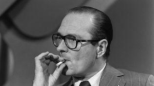 Jacques Chirac fume une cigarette, lors d'une réunion politique, à Paris, le 17 juin 1975. (GEORGES BENDRIHEM / AFP)