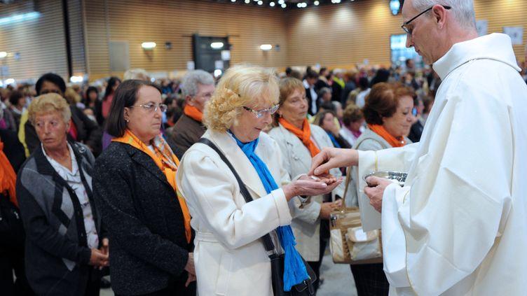 Des catholiques communient lors d'une messe, le 14 octobre 2012, à Lyon (Rhône). (PHILIPPE MERLE / AFP)