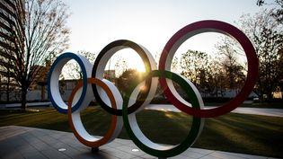 Les anneaux olympiques devant le Japan National Stadium. Les Jeux olympiques de Tokyo 2020 sont repoussés d'un an à cause de la pandémie de coronavirus. (BEHROUZ MEHRI / AFP)