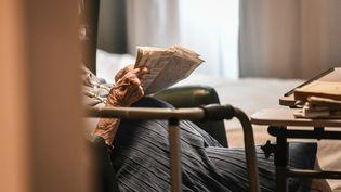 La résidente d'un Ehpad lit son journal dans sa chambre. (STEPHANE DE SAKUTIN / AFP)