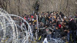 Des migrants à la frontière entre la Turquie et la Grèce, le 2 mars 2020. (GOKHAN BALCI / ANADOLU AGENCY / AFP)