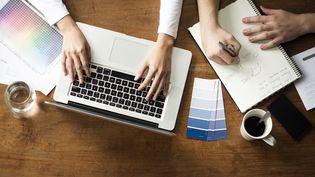 Un homme et une femme travaillent ensemble sur un ordinateur. Photo d'illustration. (FREDERIC CIROU / MAXPPP)