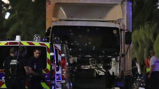 Des policiers se tiennent devant le camion - dont le pare-brise est criblé de balles - qui a foncé dans la foule sur la Promenade des Anglais à Nice (Alpes-Maritimes), le 14 juillet 2016. (VALERY HACHE / AFP)
