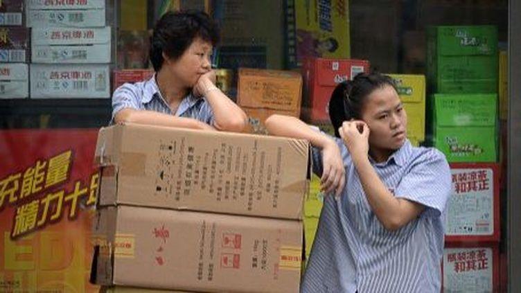 Deux Chinoises devant une boutique de Pékin, le 25 Juin 2013. (AFP PHOTO / WANG ZHAO)