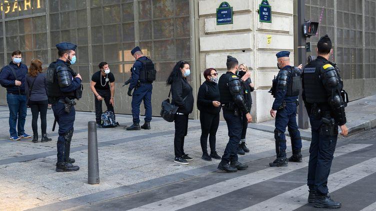 """Des gendarmes contrôlent des personnes sur les Champs-Elysées le 12 septembre 2020 en marge d'une manifestation des """"gilets jaunes"""" à Paris. (ESTELLE RUIZ / HANS LUCAS / AFP)"""
