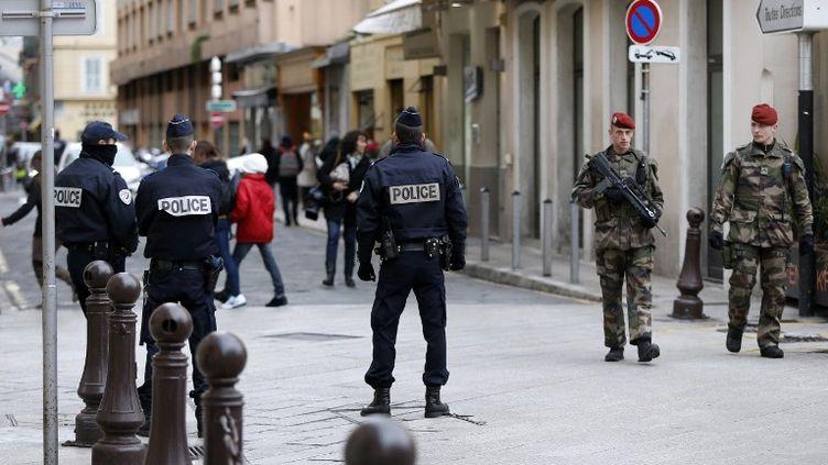 Les forces de l'ordre patrouillent devant le bâtiment où Moussa Coulibaly a agressé à l'arme blanche trois militaires, mercredi 4 février 2015. (VALERY HACHE / AFP)