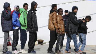 Un groupe de migrants s'apprête à embarquer dans un ferry à Lampedusa, le 20 février 2015. (ALESSANDRO BIANCHI / REUTERS)