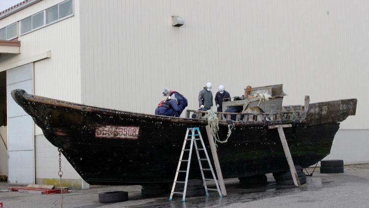 Des gardes-côtes japonais photographiés le 24 novembre 2015, en train d'examiner un des bateaux en bois transportant des cadavres, retrouvé au large des côtes de l'archipel. (AFP)