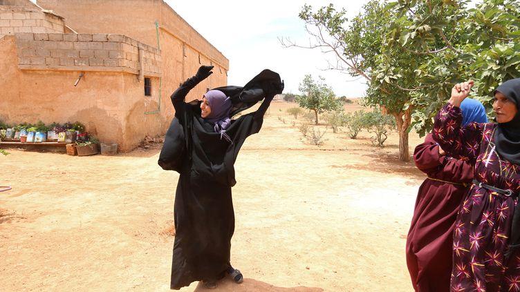 Une habitante enlève son voile intégral, après le départ de l'Etat islamique et la prise de contrôle de son village près deMinbej en Syrie par lesForces démocratiques syriennes, le 9 juin 2016. (RODI SAID / REUTERS)