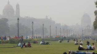 Des personnes se détendent, le 2 décembre 2015, sur les pelouses du Rajpath, à New Delhi (Inde), devantles bâtiments du gouvernement enveloppés d'un épais brouillard. (PRAKASH SINGH / AFP)