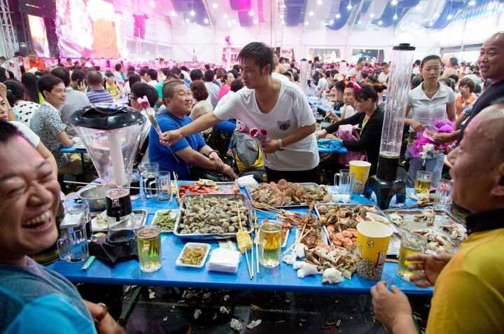 Des festivaliers mangent des fruits de mer lors de la 24e Oktoberfest de Qingdao, en Chine, le 16 août 2014. (FRISO GENTSCH / DPA / AFP)