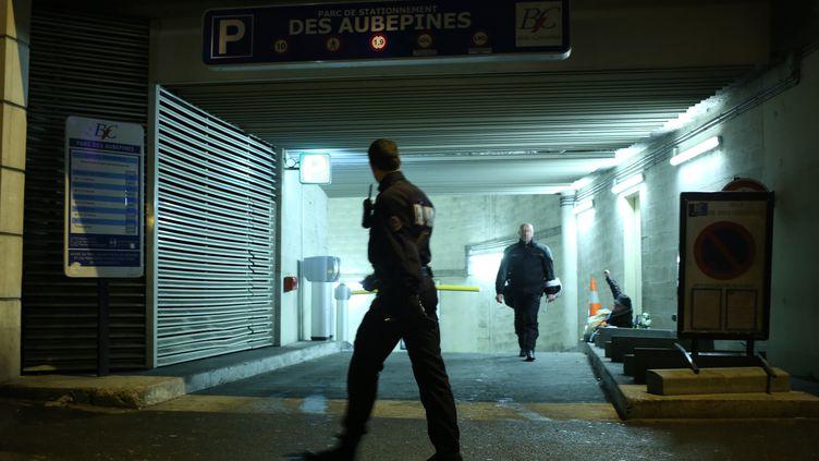 Un policier marche devant l'entrée du parking où un homme a été arrêté dans l'enquête sur le tireur parisien, à Bois-Colombes (Hauts-de-Seine), le 20 novembre 2013. (KENZO TRIBOUILLARD / AFP)