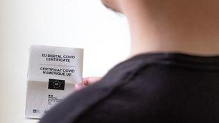 Un homme tient un certificat officiel numérique, servant de pass sanitaire dans l'Union européenne (photo d'illustration). (MAUD DUPUY / HANS LUCAS / AFP)