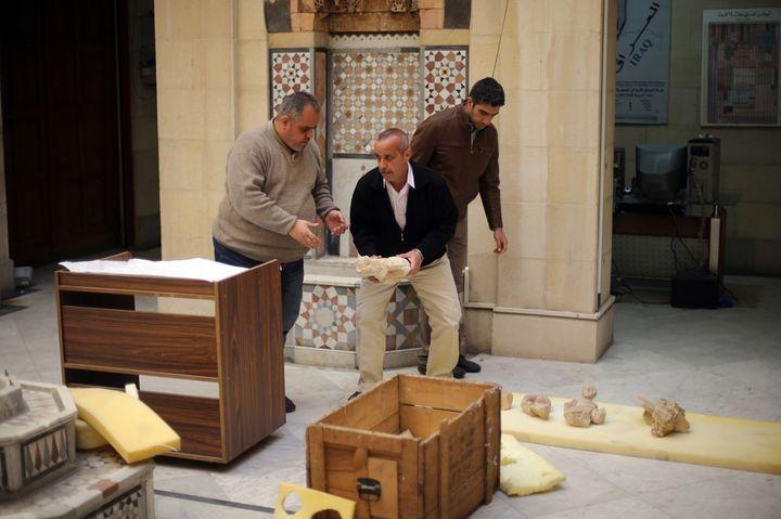 Des employés du musée de Damas emballent des statues antiques avant de les entreposer dans des boîtes (24 mars 2015)  (Joseph Eid / AFP)