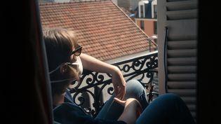 Une femme confinée sur le rebord de sa fenêtre, à Paris, le 7 avril 2020. (JULIETTE PAVY / HANS LUCAS / AFP)