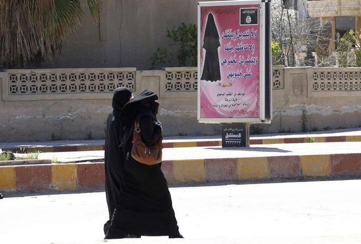 A Raqqa (Syrie),le 31 mars 2014,des femmes intégralement voilées passent devant un panneau publicitaire sur lequel est affiché la loi de l'Etat islamique. (REUTERS)