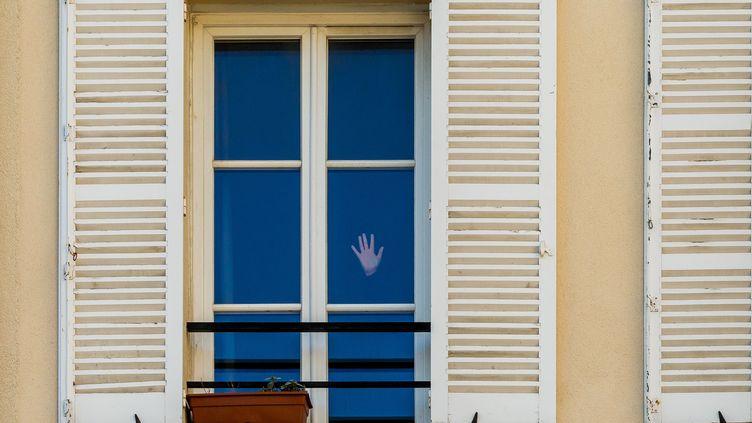 Une personne confinée chez elle, le 22 mars 2020 à Paris. (OMAR HAVANA / HANS LUCAS / AFP)