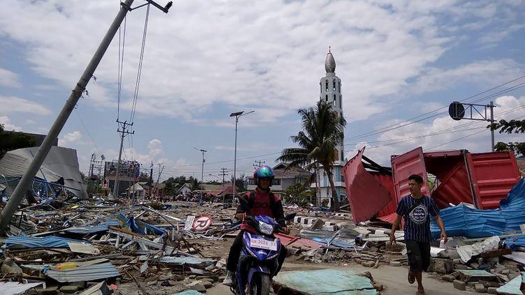 Des habitants de Palu (Indonésie) progressent au milieu des débris, samedi 29 septembre 2018, après le passage d'un puissant tsunami danscette ville de 350 000 habitants située sur l'île de Célèbes. (MUHAMMAD RIFKI / AFP)