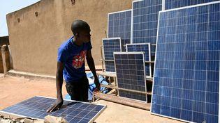Un marchand de panneaux solaires dans une rue de Ouagadougou, la capitale du Burkina Faso. Le marché a explosé ces dernières années dans le pays.Lesolaire compensela faiblesse du réseau électrique. (ISSOUF SANOGO / AFP)
