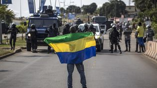 Un manifestant brandit un drapeau du Gabon devant des policiers protégeantle siège de la commission électorale, à Libreville, le 31 août 2016. (MARCO LONGARI / AFP)