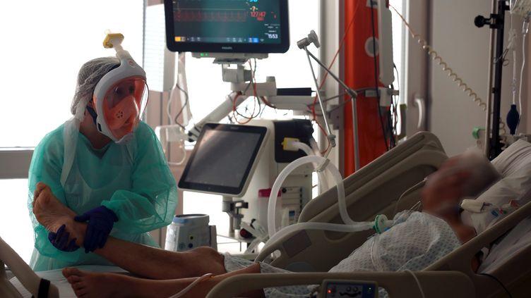 Une infirmière prend soin d'un patient dans l'unité Covid+ du service de réanimation d'un hôpital de Belfort en Franche-Comté. (LIONEL VADAM  / MAXPPP)