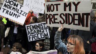 Des manifestants déroulent des banderoles anti-Trump à Washington le 20 janvier 2017 (REUTERS et APTN)