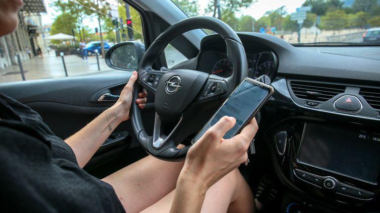 L'utilisation du portable au volant. Illustration. (NICOLAS GUYONNET / HANS LUCAS)