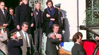Le cercueil de Claude Erignac quitte la préfecture d'Ajaccio, le 8 février 1998, sous les yeux de Dominique Erignac et de ses enfants, Charles-Antoine et Marie-Christophine. (GEORGES GOBET / AFP)