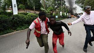 Des clients fuientle complexe hôtelier attaqué à Nairobi au Kenya, le 15 janvier 2019. (SIMON MAINA / AFP)