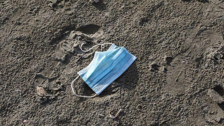 Un masque chirurgical sur le sable de la plage de Finikoudes, à Larnaca (Chypre), le 4 mai 2020. (CHRISTINA ASSI / AFP)