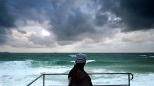 Une personne regarde la mer, le 24 octobre 2006 à Saint-Malo, alors que le quart nord-ouest de la Francesubissait des vents violents. (MARTIN BUREAU / AFP)