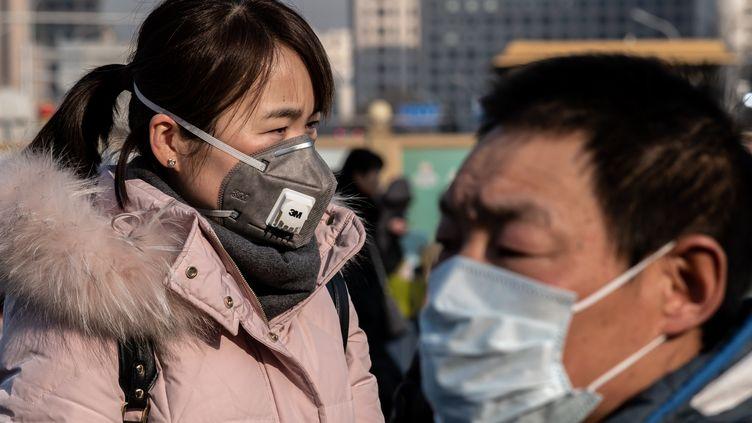 Une femme portant un masque de protection passe à côté d'un officier de police paramilitaire devant la gare de Pékin en Chine, le 21 janvier 2020 (photo d'illustration). (NICOLAS ASFOURI / AFP)