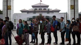 Des Népalais attendent un bus, à Katmandou (Népal), pour quitter la ville, mercredi 29 avril 2015. (MANAN VATSYAYANA / AFP)