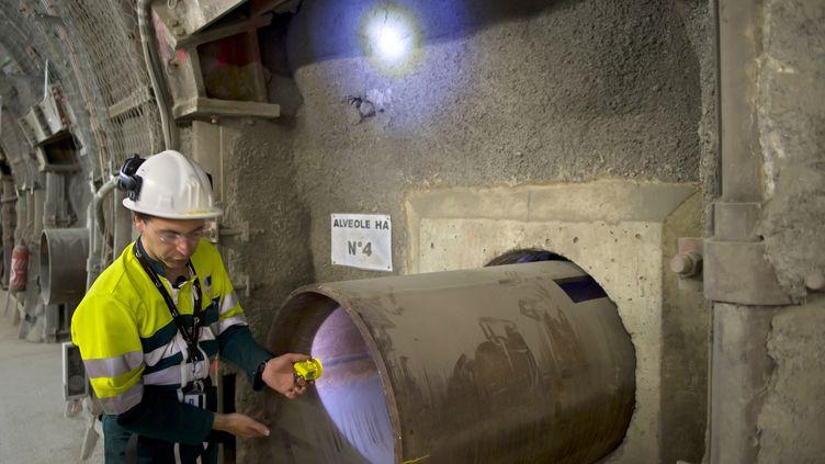 Un employé montre une alvéole destinée à accueillir des déchets nucléaires, dans le laboratoire souterrain de Bure (Meuse), le 28 juin 2011. (JEAN-CHRISTOPHE VERHAEGEN / AFP)