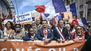 Le dirigeant des Patriotes, Florian Philippot (au centre), et le le chef de Debout la France, Nicolas Dupont-Aignan, défilent lors d'une manifestation contre le pass sanitaire près de l'Ecole militaire, à Paris, le 7 août 2021. (STEPHANE DE SAKUTIN / AFP)