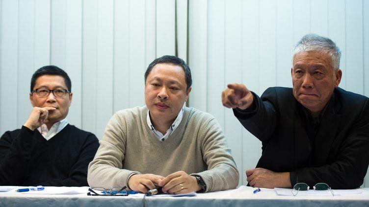 Benny Tai (centre) a annoncé, mardi 2 décembre, qu'il allait, avec les deux autres leaders du mouvement, se rendre aux autorités. (JOHANNES EISELE / AFP)