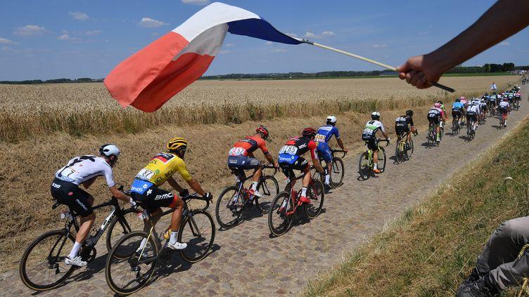 Un spectateur fait un signe avec un drapeau français, lors du passage sur lespavés des cyclistes, dans la neuvième étapedu 105e Tour de France, entre Arras et Roubaix (Nord), le 15 juillet 2018. (DAVID STOCKMAN/BELGA MAG)