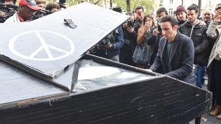 Un pianiste amateur joue devant le Bataclan à Paris, le samedi 14 novembre, au lendemain des attentats sanglants qui ont frappé la capitale française. (UWE ANSPACH / DPA / AFP)