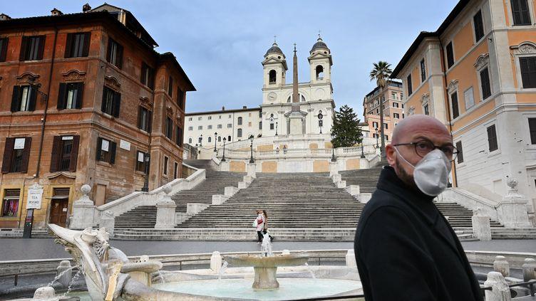 Un homme portant un masque de protection marche sur la Piazza di Spagna, à Rome (Italie), le 12 mars 2020. (ALBERTO PIZZOLI / AFP)