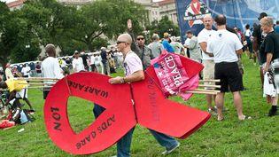 Un activiste porte un ruban rouge géant lors d'un rassemblement en marge de la 19e conférence internationale sur le sida, à Washington (Etats-Unis), le 22 juillet 2012. (NICHOLAS KAMM / AFP)